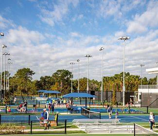 A sunny day at the USTA national campus with players and spectators on the courts
