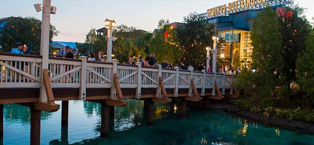 Pedestrians cross a footbridge during twilight at Disney Springs