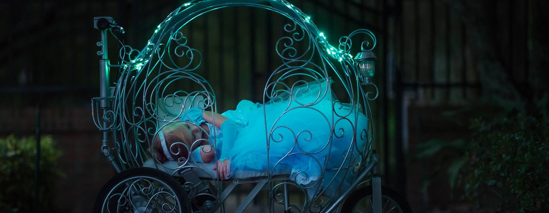 A girl dressed as a princess sleeping in a lit carriage from Princess Carriage Rentals at night