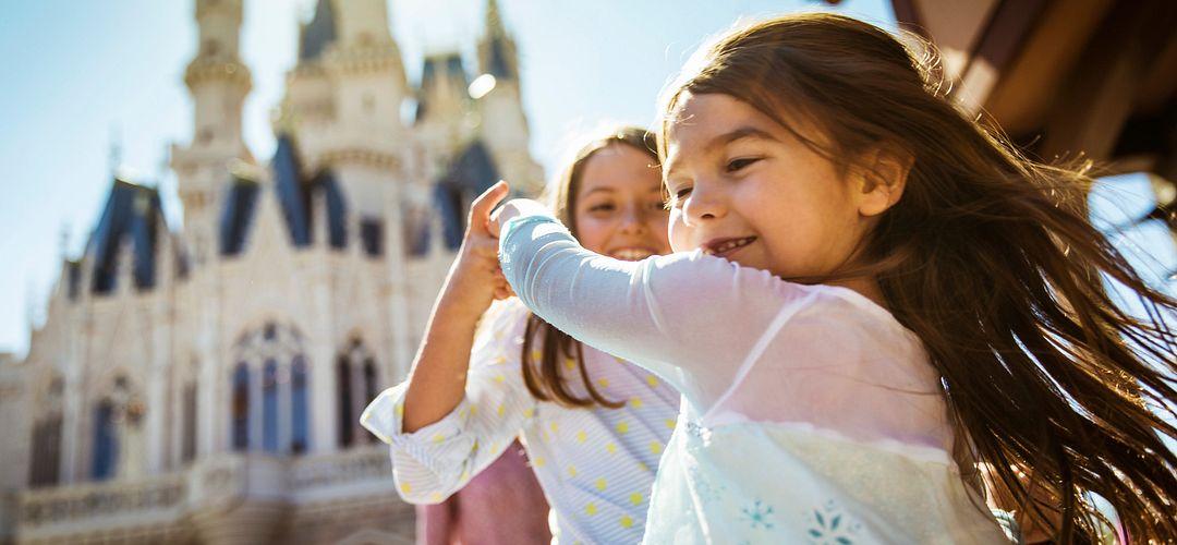 Hermanas jóvenes giran y bailan a la luz del sol con Cinderella & rsquo; s Castle en el fondo.