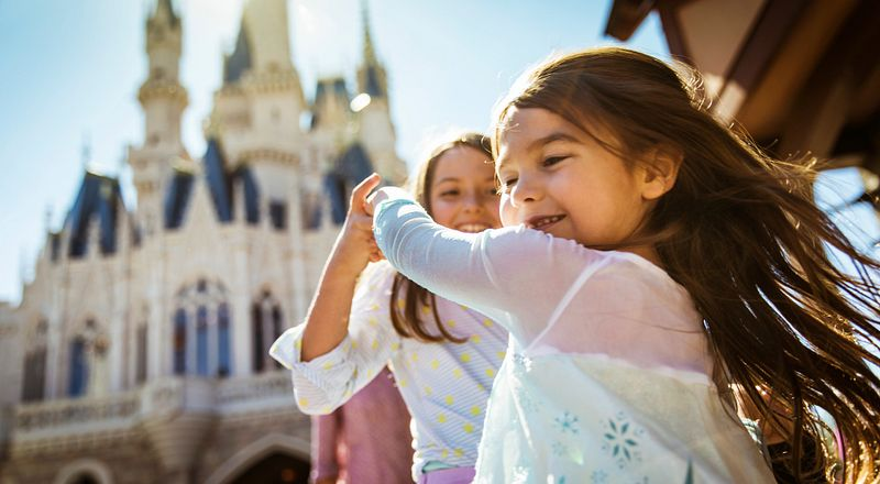 Young sisters twirl and dance in the sunlight with Cinderella's Castle in the background.