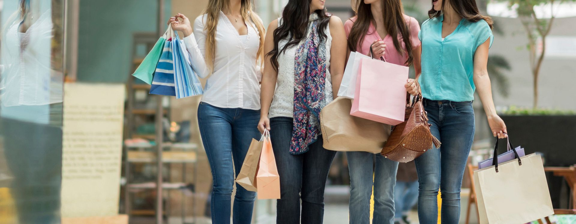 Women walking together holding shopping bags
