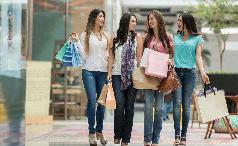 A group of women walking at a shopping center and holding bags in Orlando