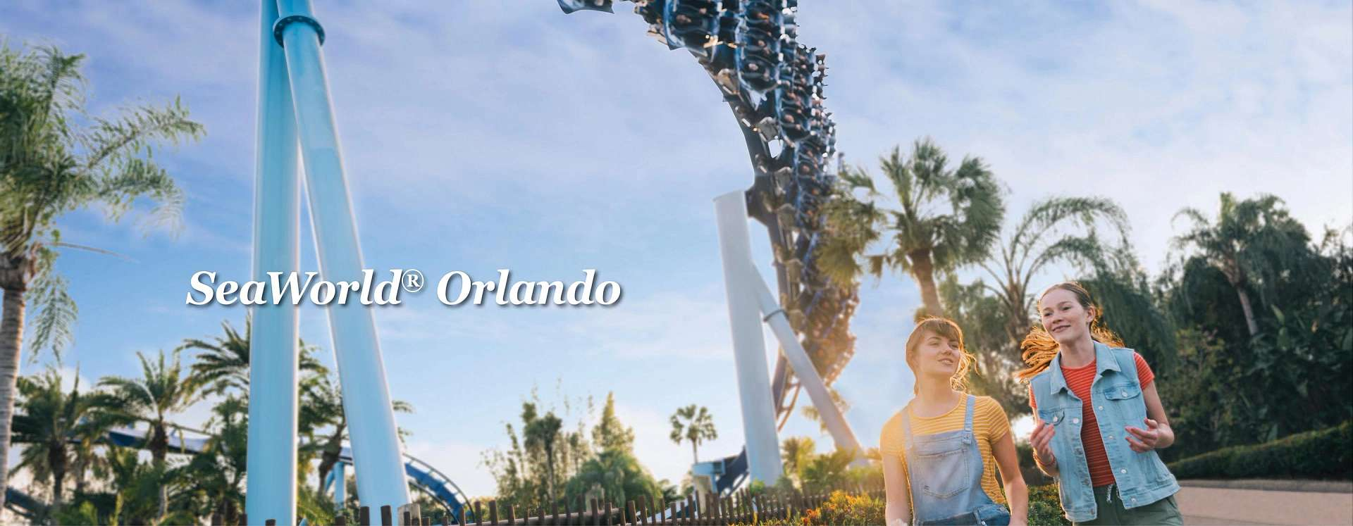 Two teenage girls walking together in SeaWorld Orlando while the Manta rollercoaster zooms by