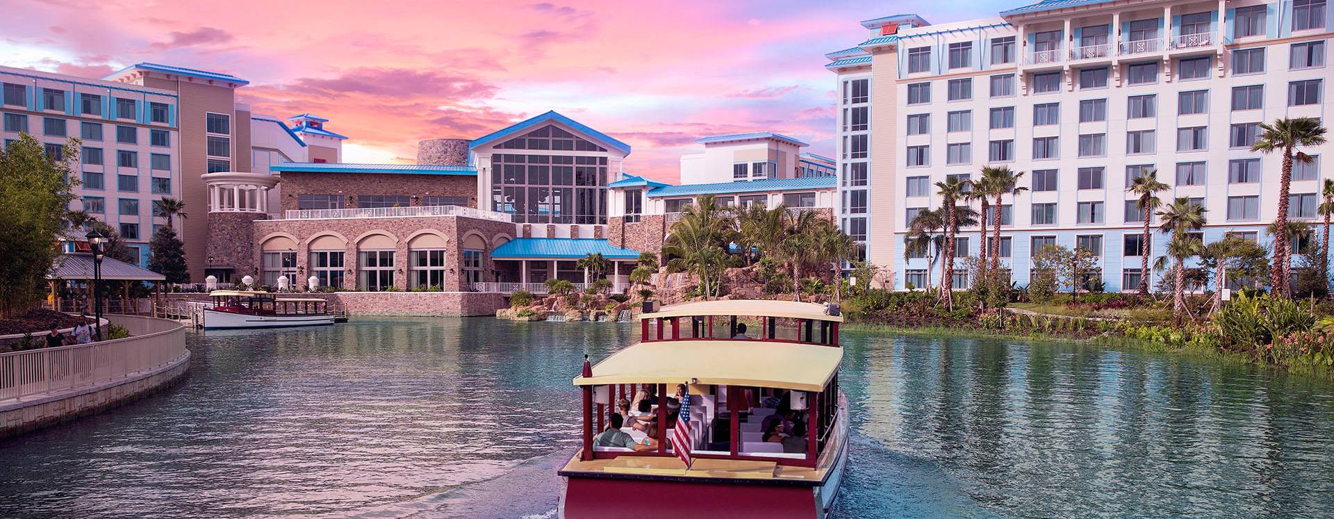 A boat arriving during sunset at Loews Sapphire Falls Resort at Universal Orlando&trade.