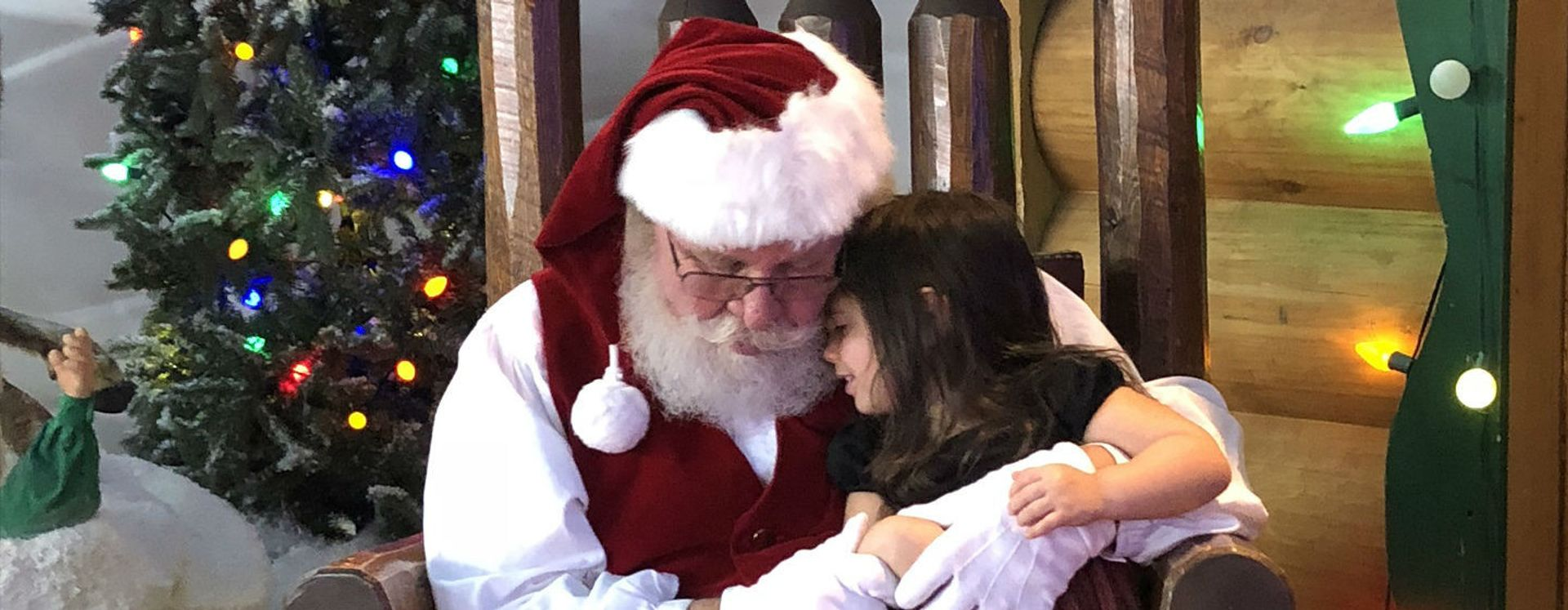 Santa Claus holding girl seated on his laps