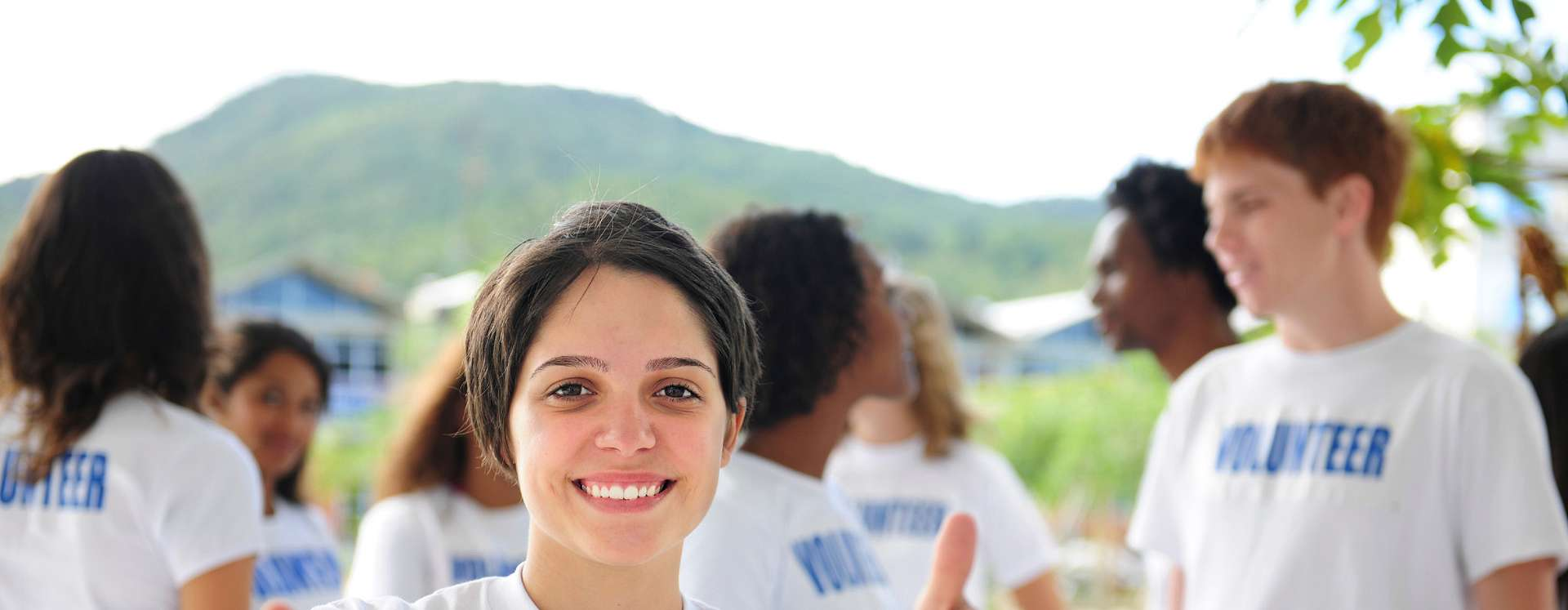 A young, smiling female volunteer showing both thumbs up with a group of other volunteers in the background.
