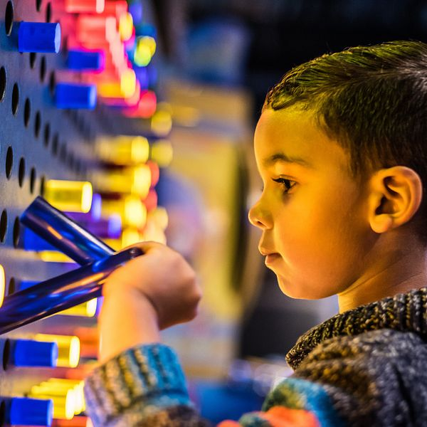 A young boy experiencing the interactive entertainment at WonderWorks Orlando.