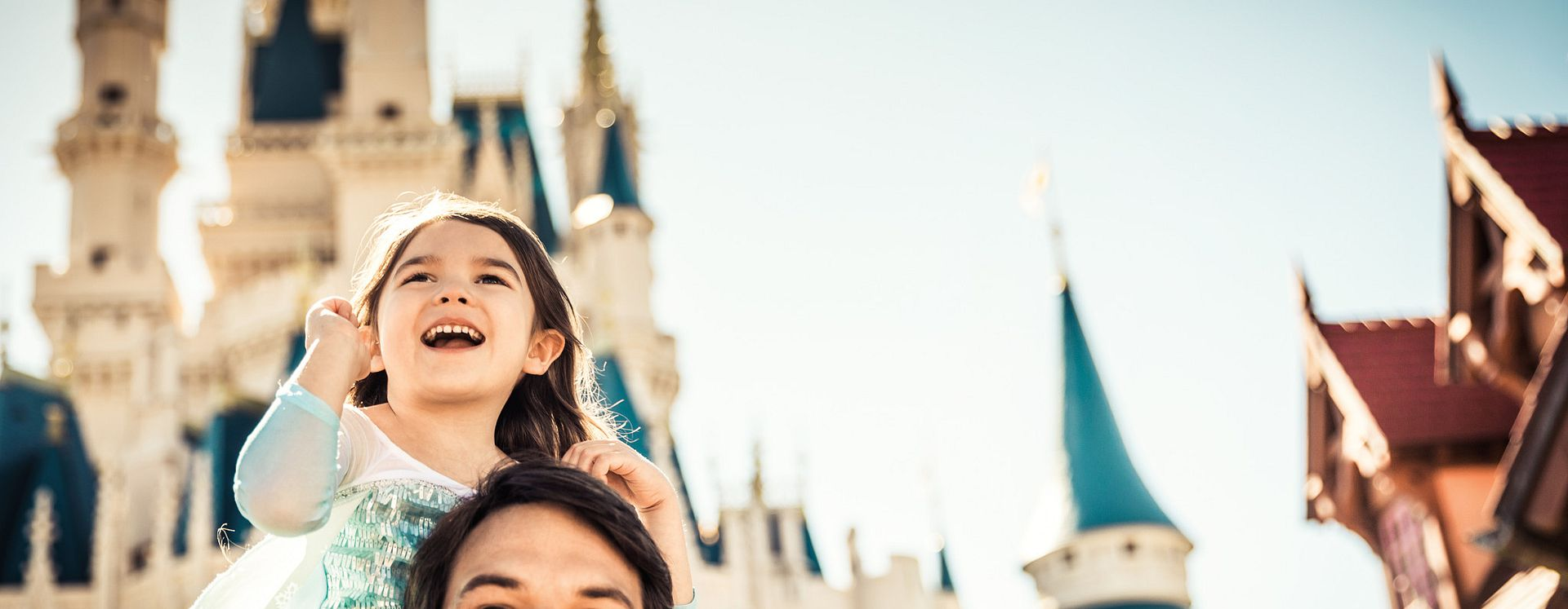 Young girl dressed as a princess and riding on her father's shoulders with the castle in the background at Walt Disney World