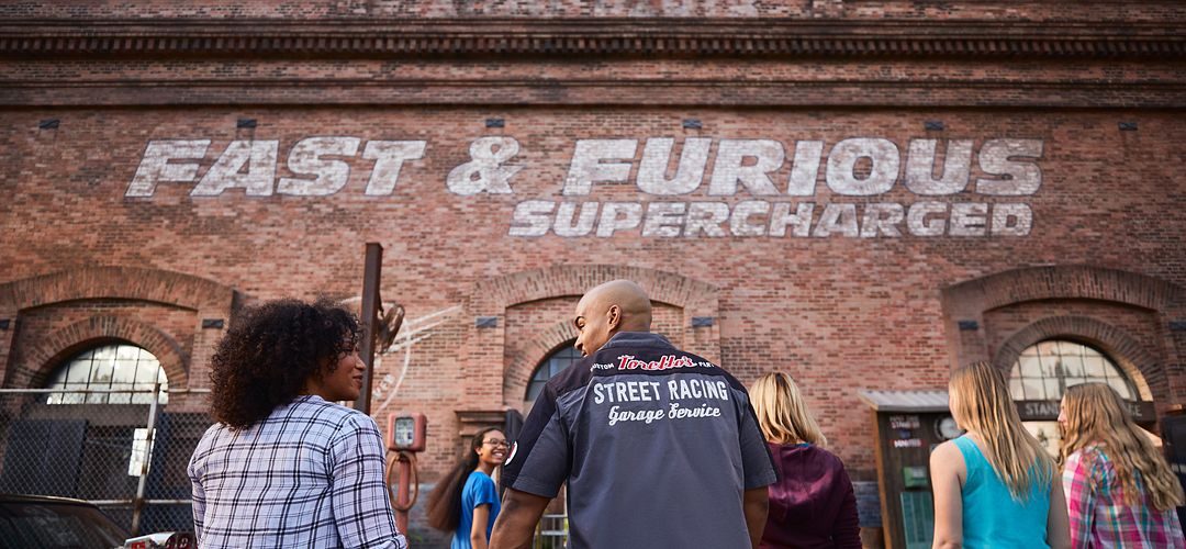 A family and park guests at the entrance of Fast & Furious Supercharged at Universal Studios in Orlando, Florida.