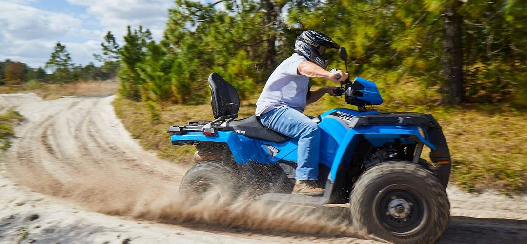 Man driving an ATV on a dirt path, surrounded by pine trees, near Orlando