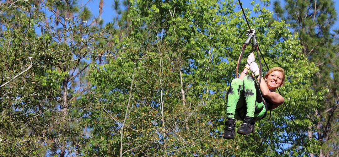 woman riding a zipline throuh a forest