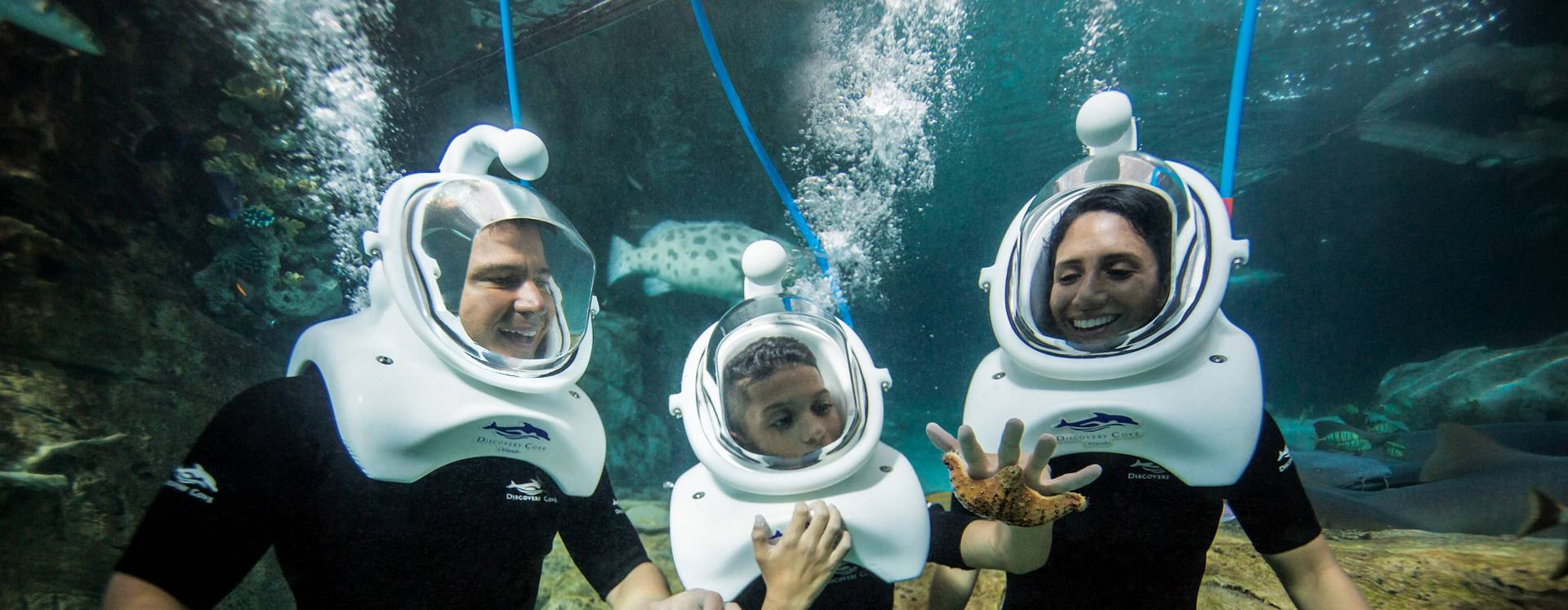 Family underwater wearing oxygen mask helmets in Discovery Cove, Orlando