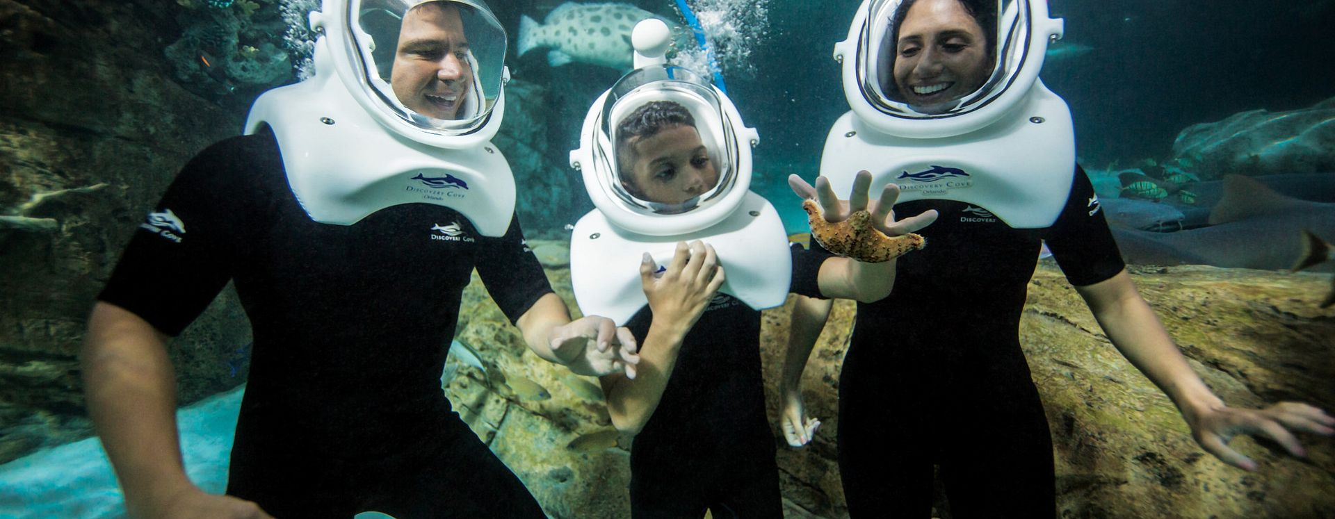 Family underwater with a oxygen mask helmet on in Disovery Cove, Orlando