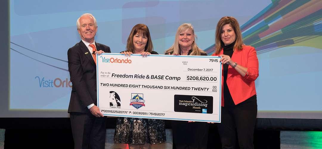 Um cheque de Magical Dining beneficiando o Freedom Ride & BASE Camp. Na Visit Orlando, temos um compromisso com a comunidade.