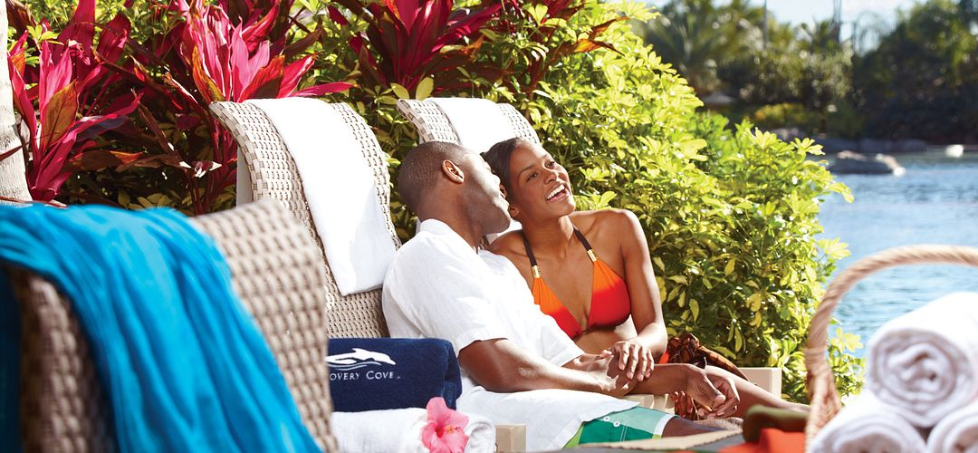A couple reclining on lounge chairs, holding hands.