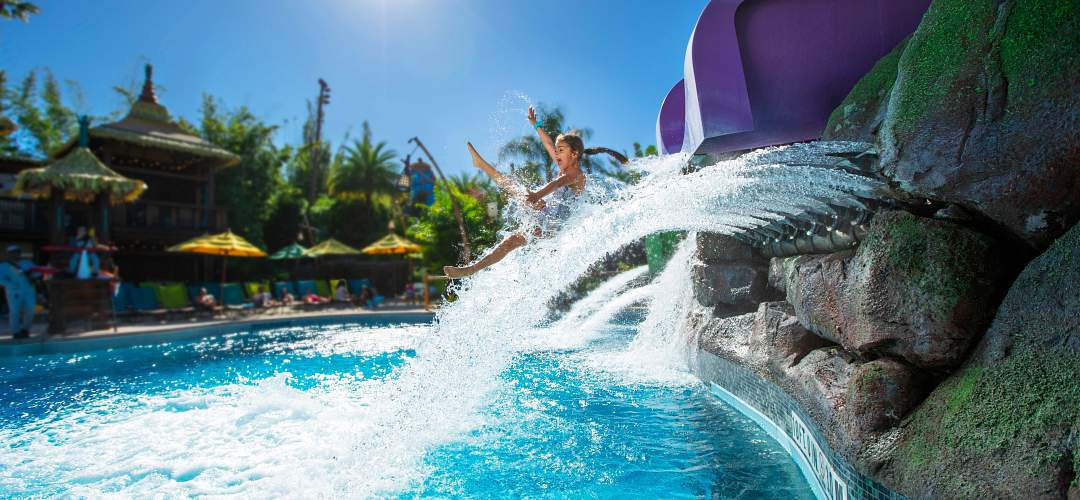 A little girl coming out of a water slide in Universal's Volcano Bay.