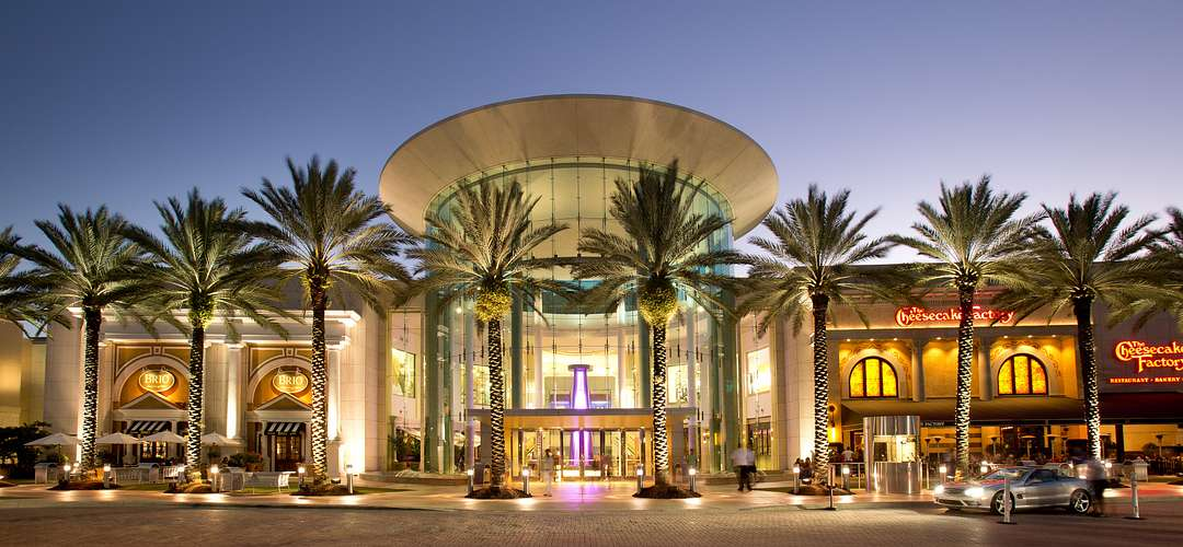 An exterior shot of the main entrance of The Mall at Millenia in Orlando at night