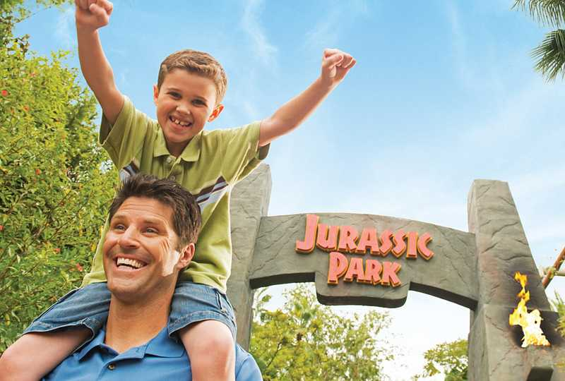 Excited boy riding on his father's shoulders in Jurassic Park at Islands of Adventure.