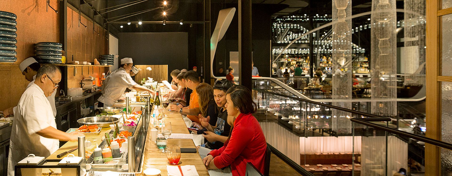 People eating at a sushi bar, while sushi chefs prepare orders, at Morimoto Asia restaurant in Disney Springs