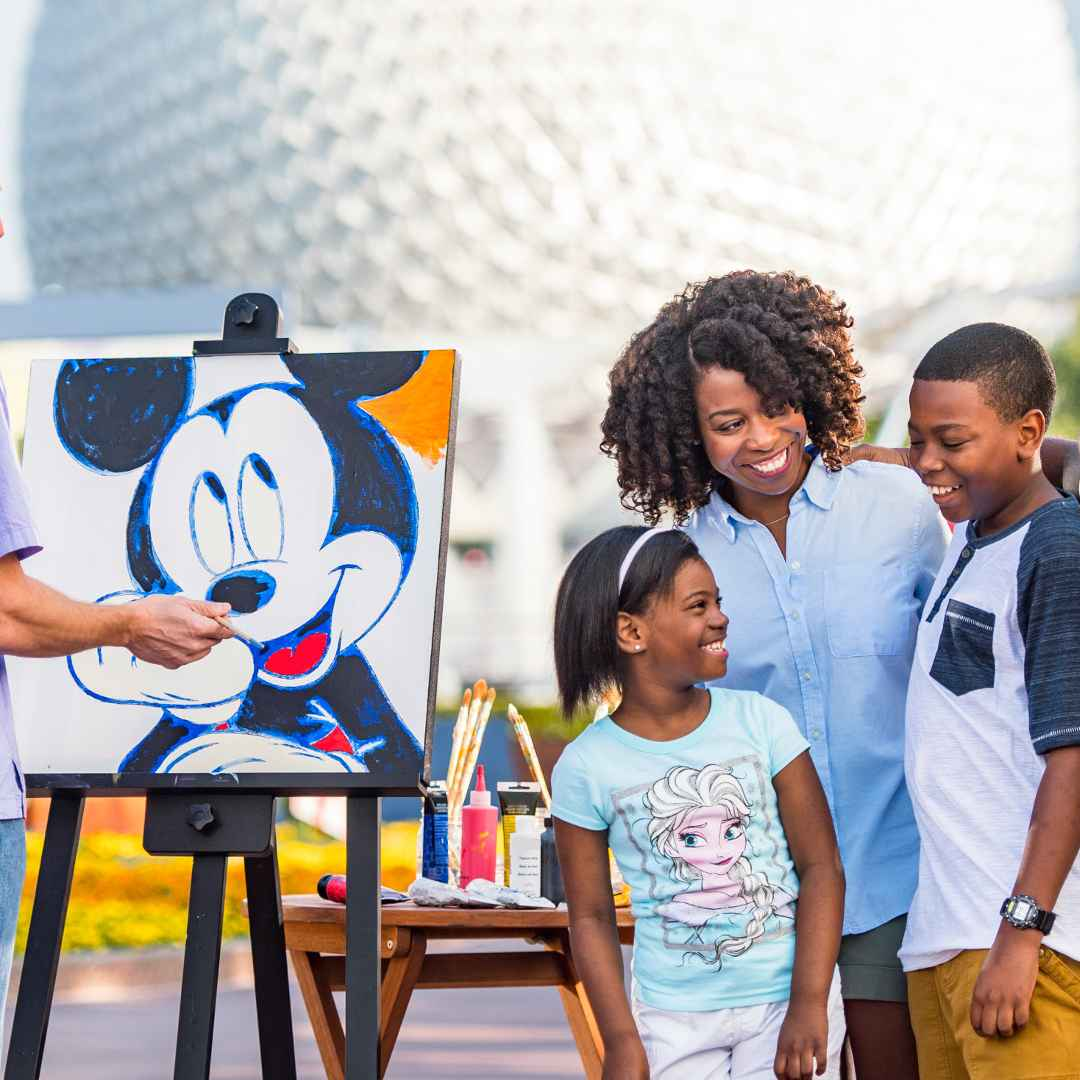 An artist in Epcot paints Mickey Mouse, while a smiling family looks at the reaction of the youngest sibling