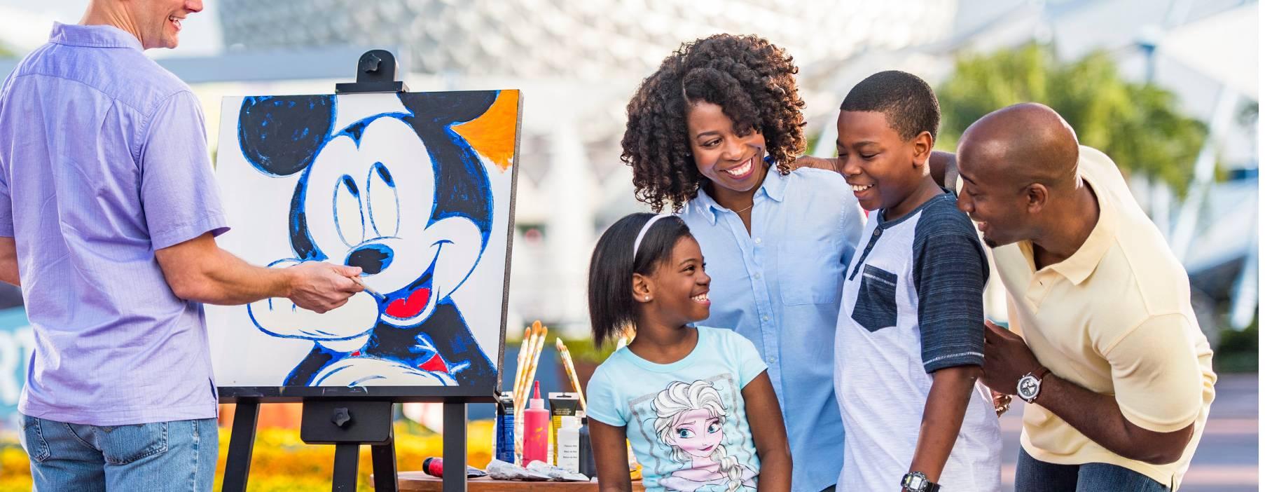 Um artista no Epcot pinta um Mickey Mouse enquanto uma família observa alegremente a reação do seu integrante mais jovem