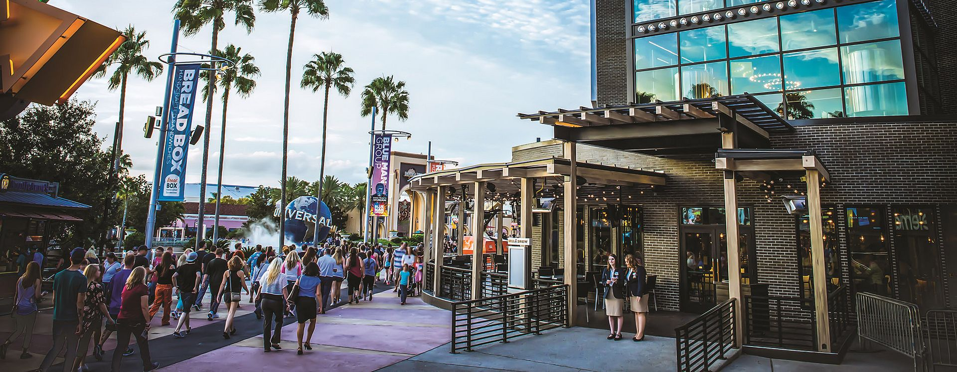 Crowds of people at Universal CityWalk walking by the NBC Sports Grill, with the Universal globe and the entrance to Universal Studios Florida in the background.