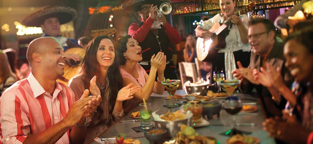 A mariachi group playing while friends sing and clap with food and drinks at the table at Antojitos.
