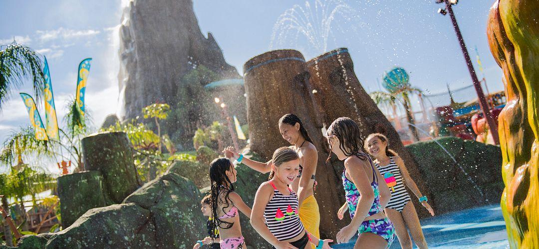 Niños reunidos en una piscina con el volcán en el fondo