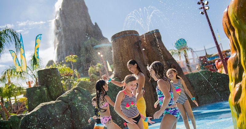 Children gathered around in a pool with the volcano in the background
