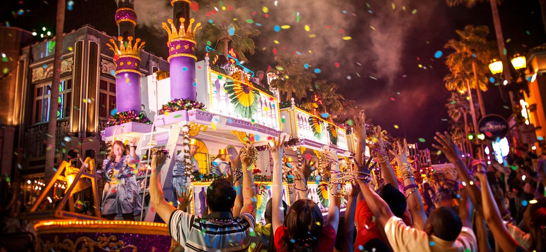 People cheering in the Universal Studios Florida Mardi Gras parade as a float goes by