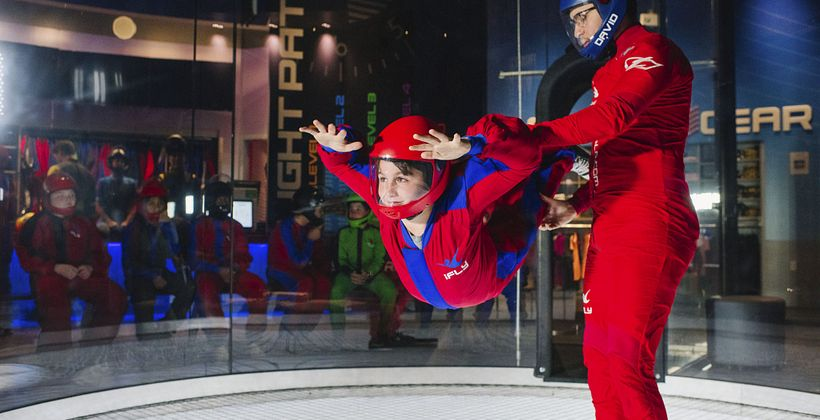 a person floating in iFLY  Orlando's vertical wind tunnel technology