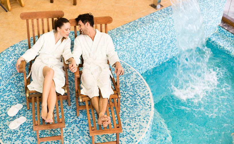 Young couple relaxing in their bath robes by a spa pool.