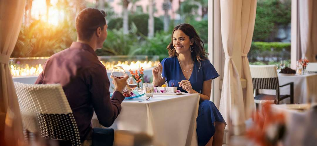 An elegantly dressed couple dining outside at The Venetian Chop House during sunset