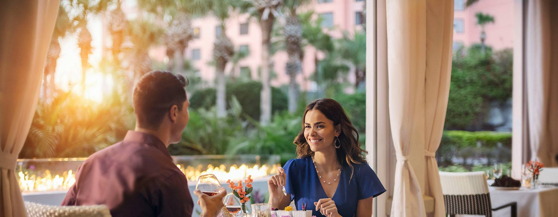 A couple enjoying the sunset while dining outdoors at The Venetian Chophouse