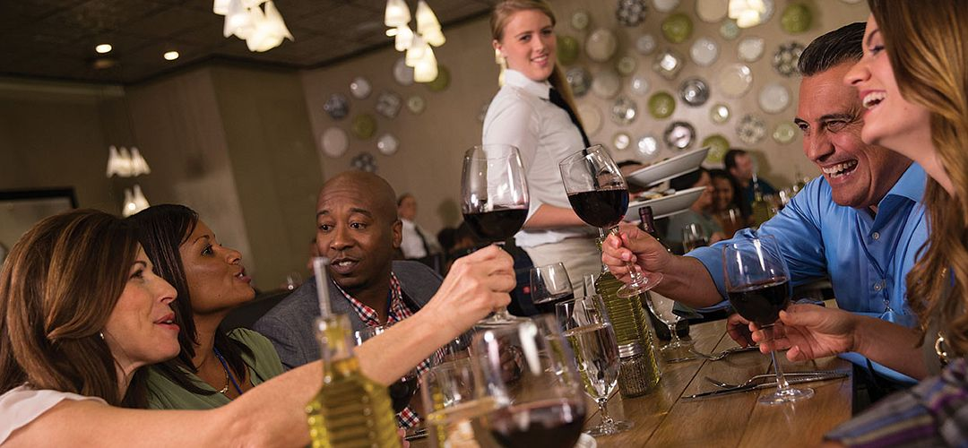 A group of people toasting with wine inside Vivo Italian Kitchen.