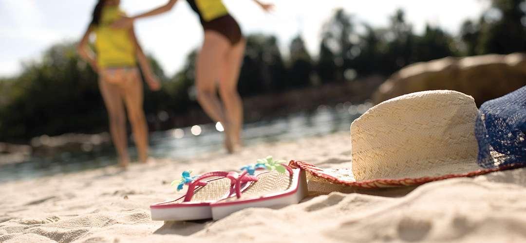 Sandálias e um chapéu na areia em primeiro plano, enquanto uma mãe e uma filha voltam para o rio no fundo.