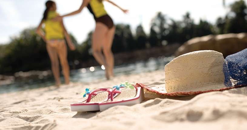 Sandals and a hat on the sand in the foreground, while a mother and daughter head back to the river in the background.