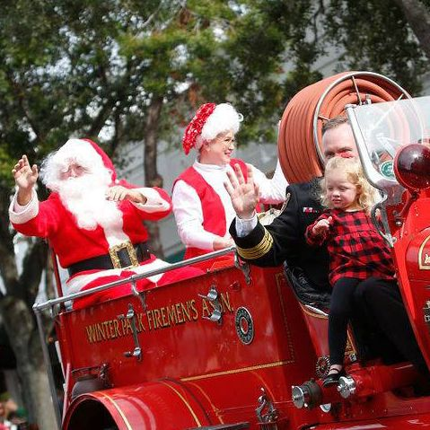 Santa rides in on a fire truck during the Winter Park Christmas Parade