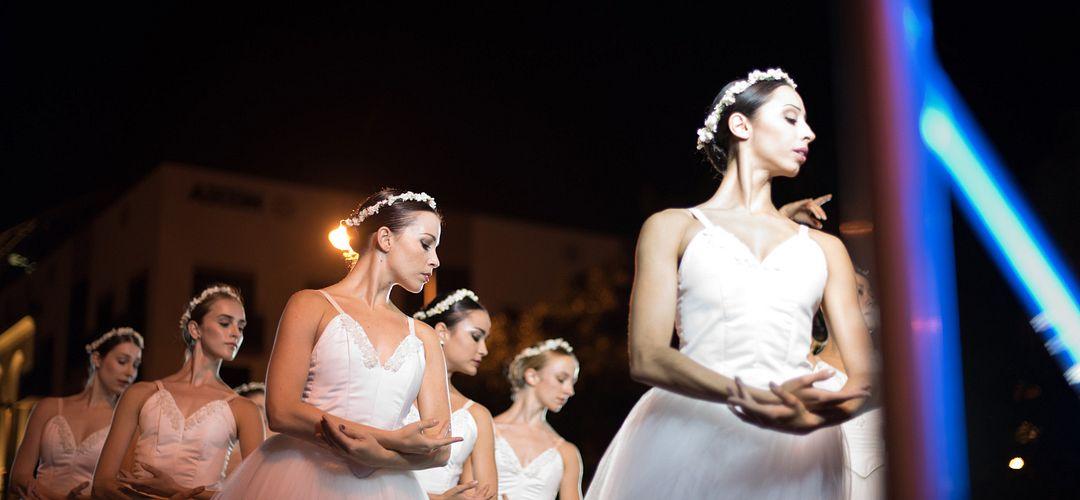 Dos personas bailando ballet con la coral en el fondo