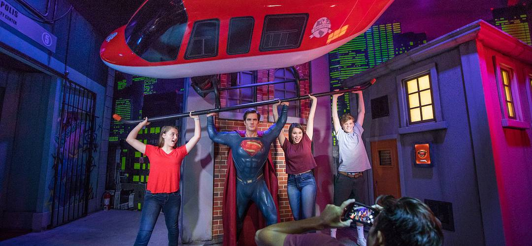 Three friends posing with Superman at Madame Tussauds on International Drive in Orlando, Florida.