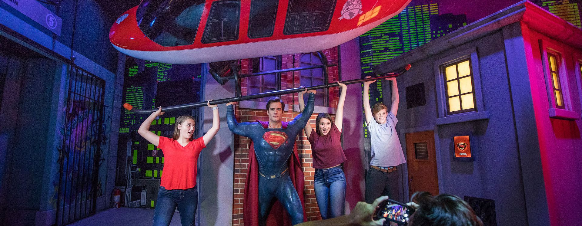 A group of friends posing with Superman holding up a helicopter at Madame Tussauds
