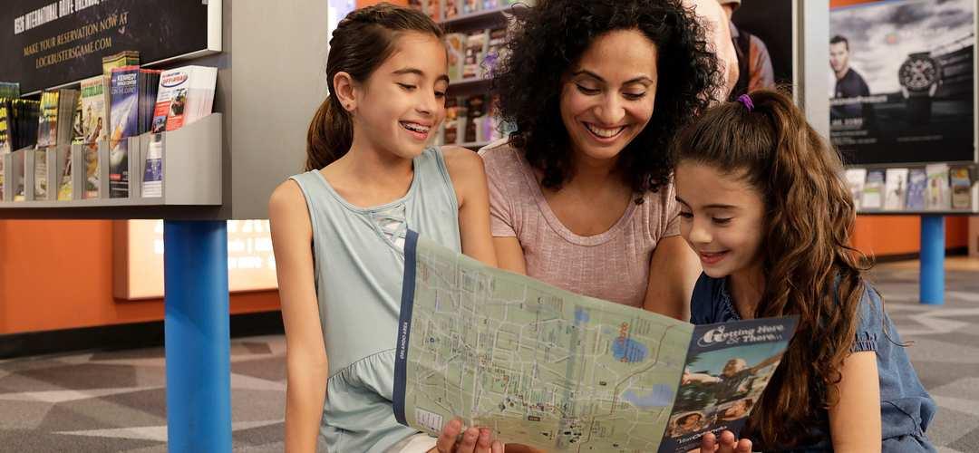 Una madre y sus hijas mirando un folleto en el centro para visitantes.