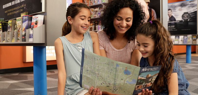 Mother and daughters planning their next adventure while reading a map of Orlando.