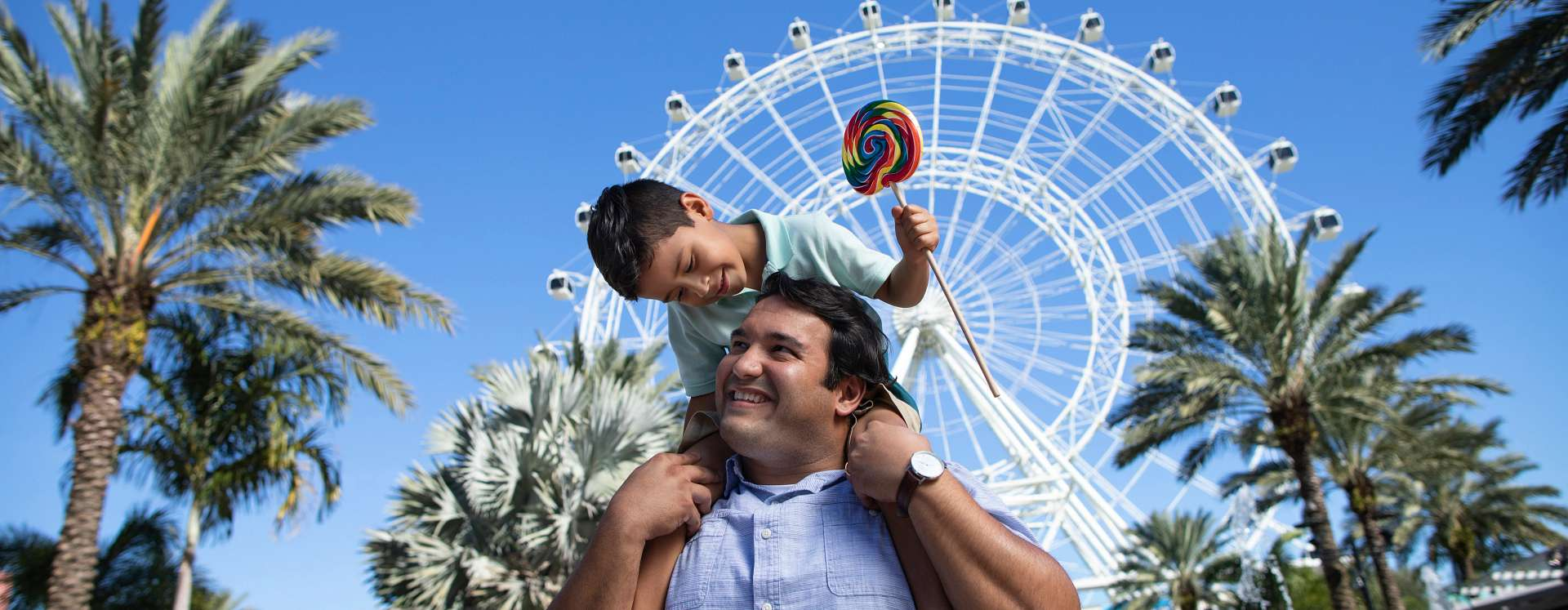 Son riding on his father's shoulders while holding a lollipop at ICON Park on International Drive in Orlando, Florida
