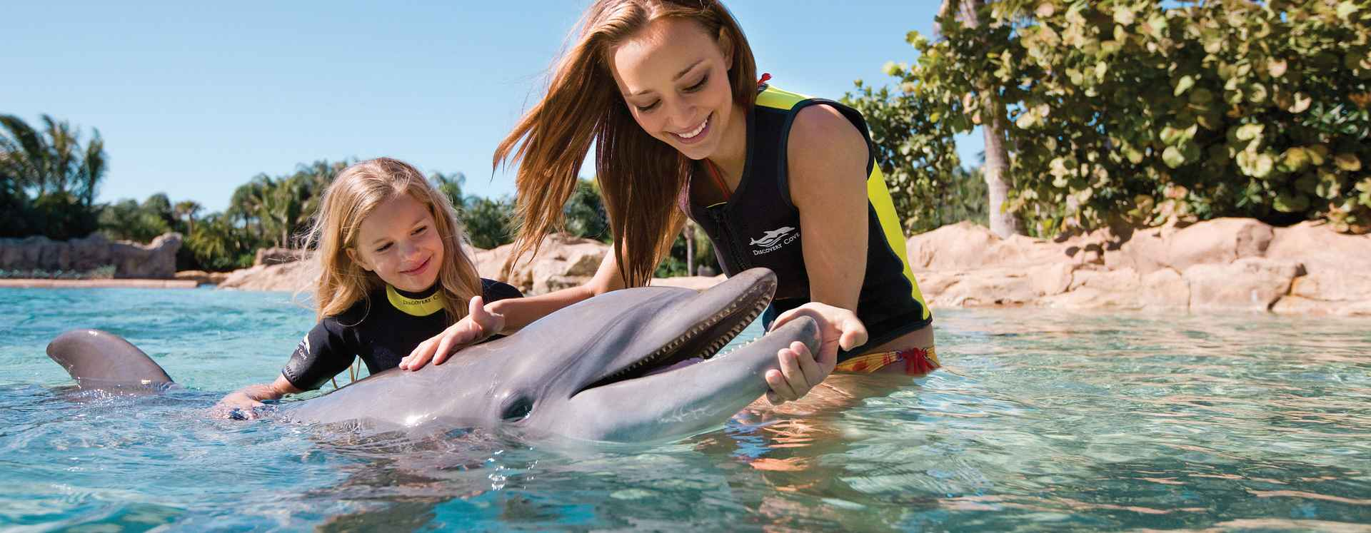 Little girl and mother playing with dolphin at Discovery Cove.