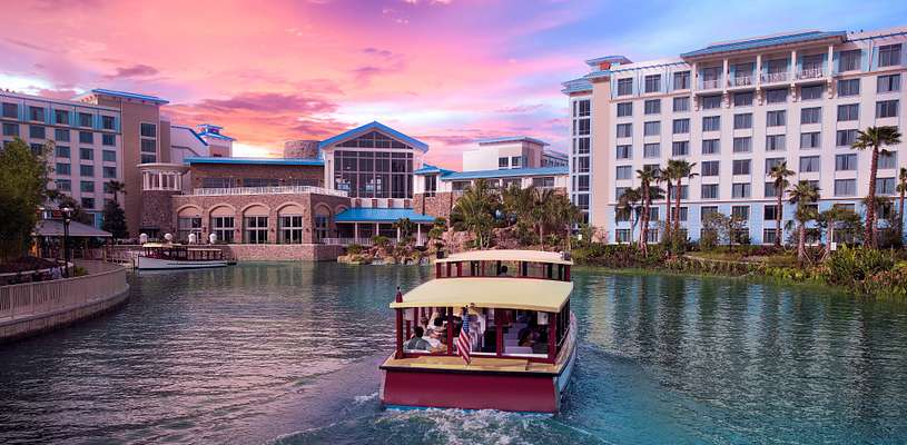 Water Taxi arriving while the sun sets behind the Loews Sapphire Falls Resort