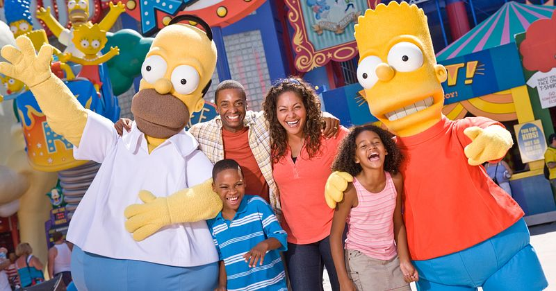 A family of four posing with Bart and Homer from The Simpsons