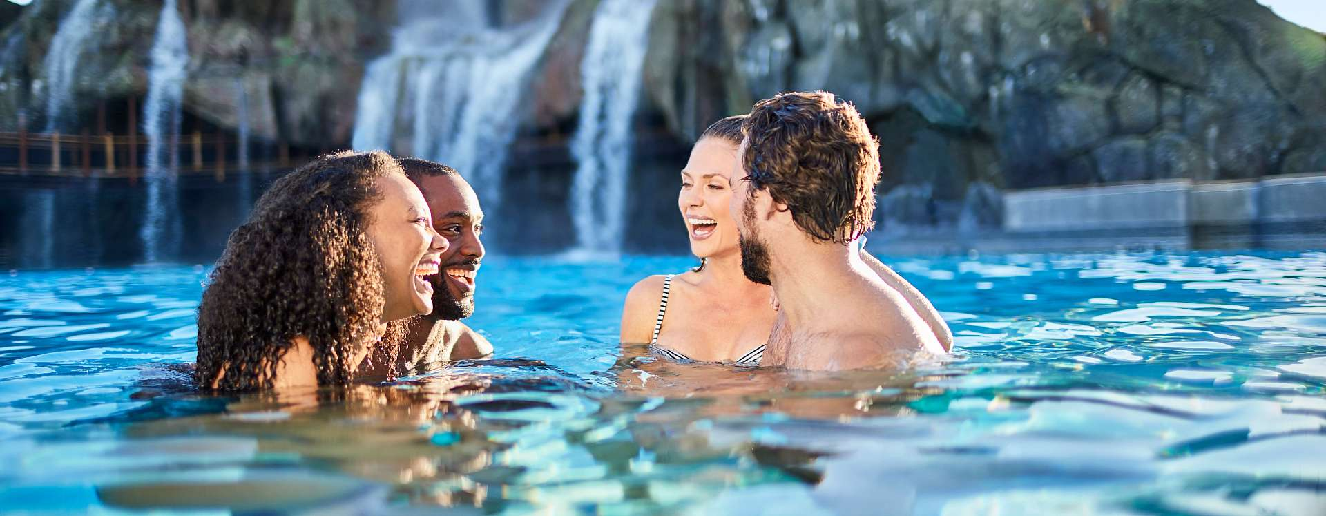 Couples having fun and relaxing in a pool at Universal's Volcano Bay