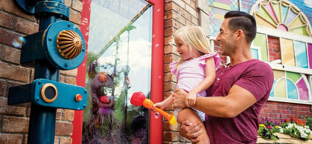 A father and daughter interacting with Sesame Street land attractions